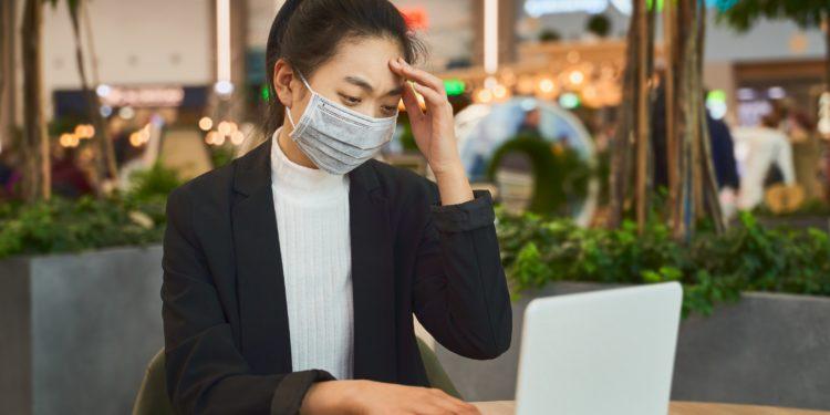 Una mujer se sienta con una mascarilla frente a un cuaderno.