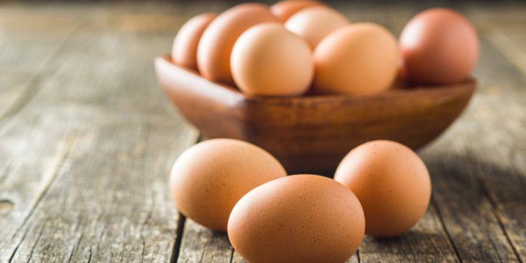 Eier in einer Holzschale und auf einem Holztisch