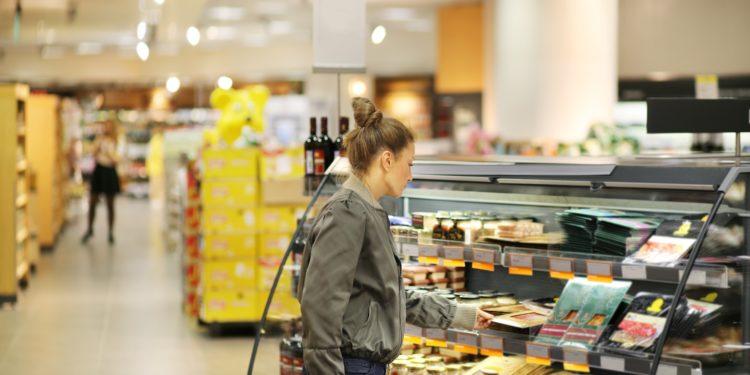 Eine Frau steht vor einem Regal im Supermarkt.