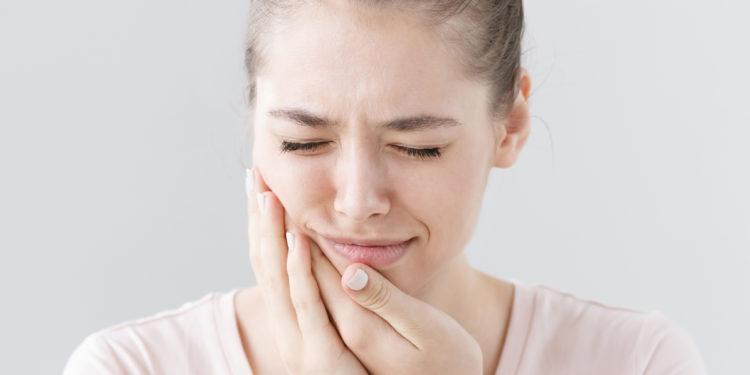 Junge Frau mit schmerzverzerrtem Gesicht hält sich ihre Hände an die Wange