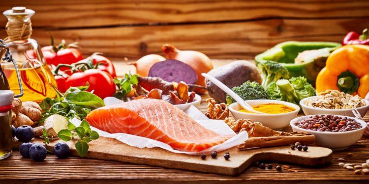 Mediterrane Lebensmittel wie Fisch, Gemüse und Olivenöl auf einem Tisch
