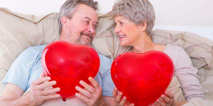 Ein älterer Paar liegt im Bett.