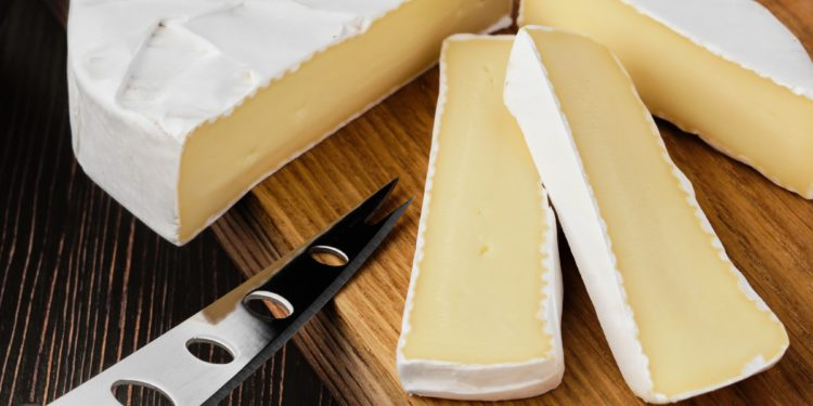 Ein angeschnittener Camembert auf einem Holzbrett mit Käsemesser