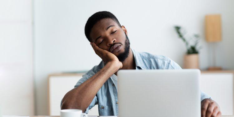 Mann stützt seinen Kopf in die Hand und sitzt mit geschlossenen Augen vor dem Laptop daneben steht eine Kaffeetasse
