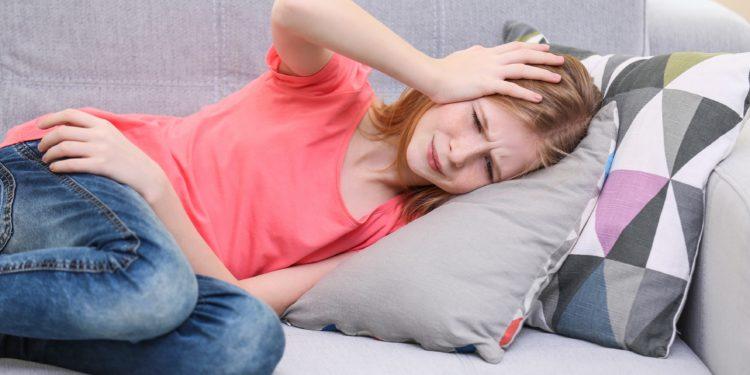 Junge Mädchen liegt mit Kopfschmerzen auf dem Sofa