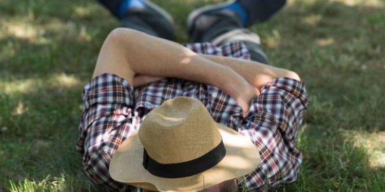 Ein Mann schläft auf einer Wiese.