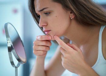 Junge Frau drückt vor einem kleinen runden Spiegel einen Pickel im Gesicht aus