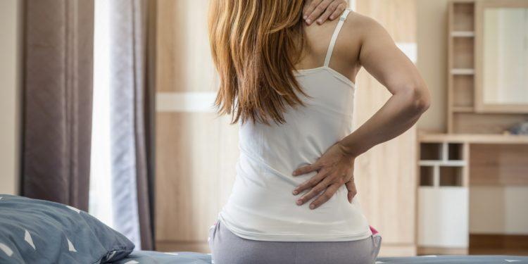 Frau sitzt auf dem Bett und fasst sich an den schmerzenden Rücken