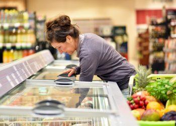 Frau holt Ware aus einer Tiefkühltheke im Supermarkt