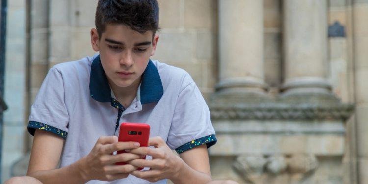 Kind benutzt Smartphone.