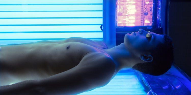 Ein junger Mann liegt im Solarium unter der Sonnenbank