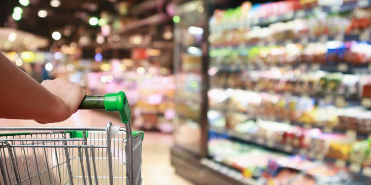 Eine Person schiebt einen Einkaufswagen durch einen Supermarkt.