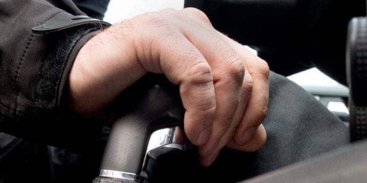 Ein Mann sitzt im Auto und hat eine Hand auf die Gangschaltung gelegt.