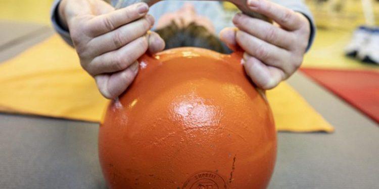 Eine Person trainiert mit einem Kugelgewicht.