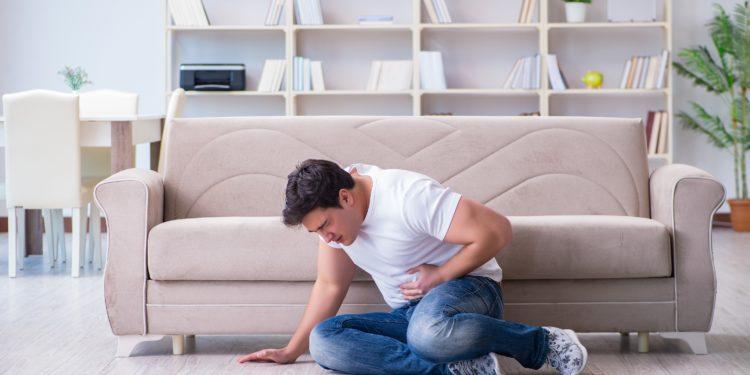 Ein Mann sitzt zusammengesunken auf dem Fußboden vor einem beigen Sofa und hält sich die Hand an den Bauch.