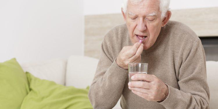 Älterer Mann nimmt eine Tablette ein