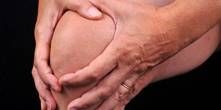 Person umklammert ihr Knie mit beiden Händen