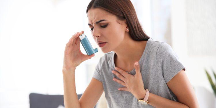 Frau hält einen Inhalator und fasst sich an den Brustkorb.