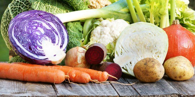 Eine Auswahl ballaststoffreicher Nahrungsmittel liegt auf einem Holztisch.