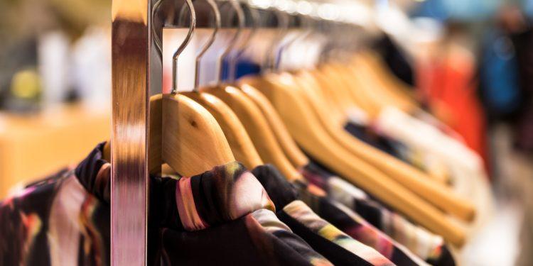 Verschiedene Kleidungsstücke hängen an Bügeln zum Verkauf bereit.