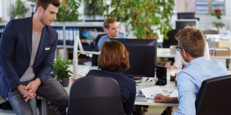 In einem Großraumbüro sitzen mehrere Mitarbeiterinnen und Mitarbeiter an einem Tisch.