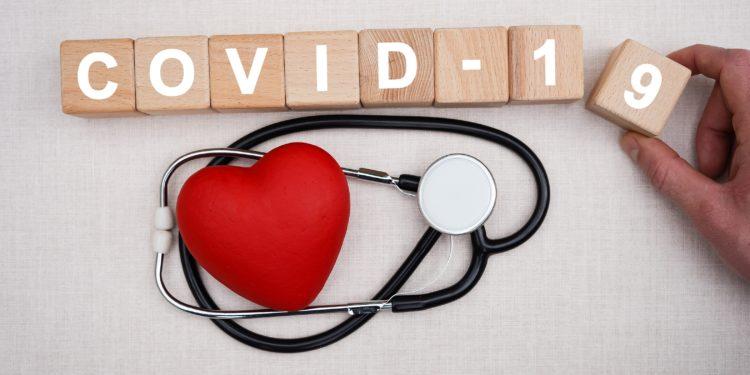 Hand legt aus Holzwürfeln den Schriftzug COVID-19 neben einem Stethoskop