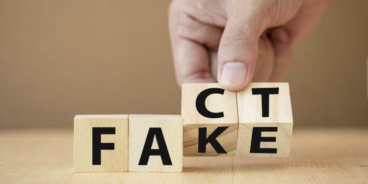 Eine Hand dreht Holzklötzchen mit Buchstaben von Fake auf Fact