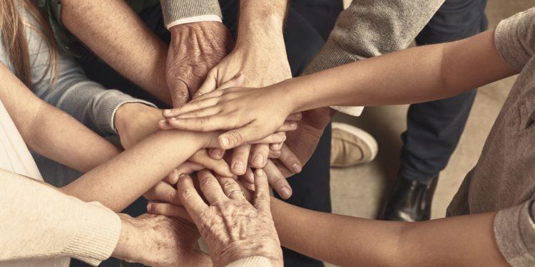 Die Hände von vielen im Kreis stehenden Personen berühren sich in der Mitte des Kreises.