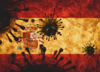 Auf einer Spanischen Flagge sind die Konturen von Viren abgebildet.