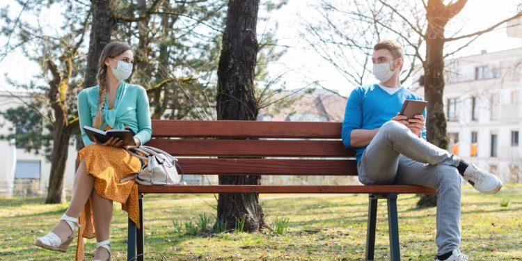 Eine Frau und ein Mann sitzen auf den jeweils äußeren Ende einer Bank und schauen sich an.
