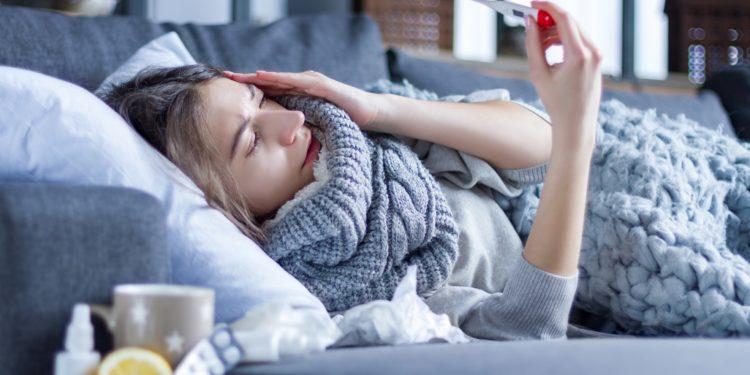 Eine Frau liegt im Bett und schaut auf ein Fieberthermometer.