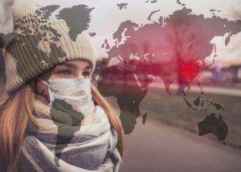 Eine Frau mit Mundschutz hinter einer Weltkarten-Illustration mit Kennzeichnung der der zentralchinesischen Provinz Hubei.
