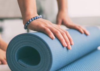Frau rollt eine Fitnessmatte in der Wohnung aus