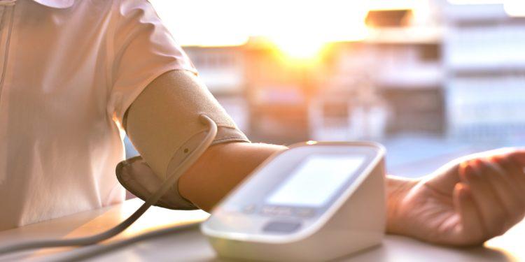 Mann misst seinen Blutdruck mit Blutdruckmessgerät