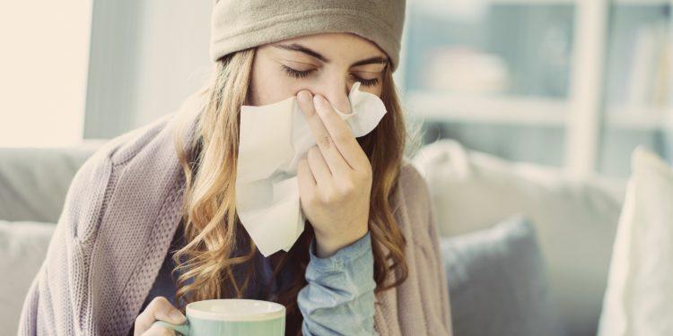Eine junge Frau hält sich ein Taschentuch vor die Nase.