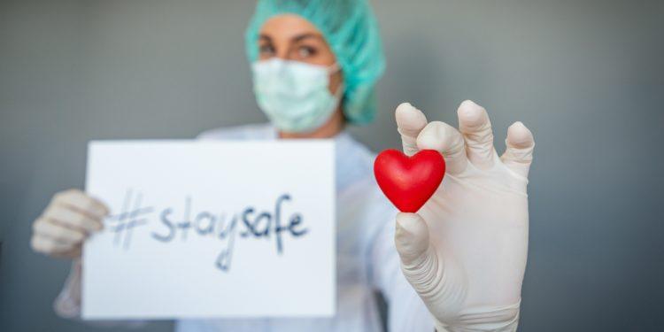 """Eine Ärztin hält ein Plastikherz in der einen Hand und in der anderen Hand ein Papier mit der Aufschrift """"stay safe""""."""