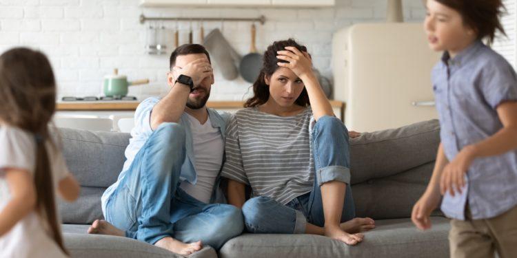 Genervte junge Eltern auf dem Sofa und zwei herumtollende Kinder