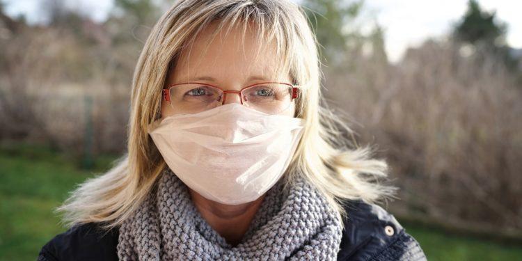 Eine blonder Frau mit Brille trägt einen Mundschutz.