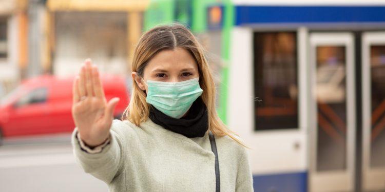 Frau mit medizinischer Gesichtsmaske macht mit der Hand das Zeichen, von ihr weg zu bleiben