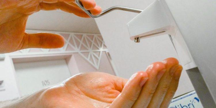 Ein Paar Hände bedienen einen Desinfektionsmittel-Spender in einem Krankenhaus.