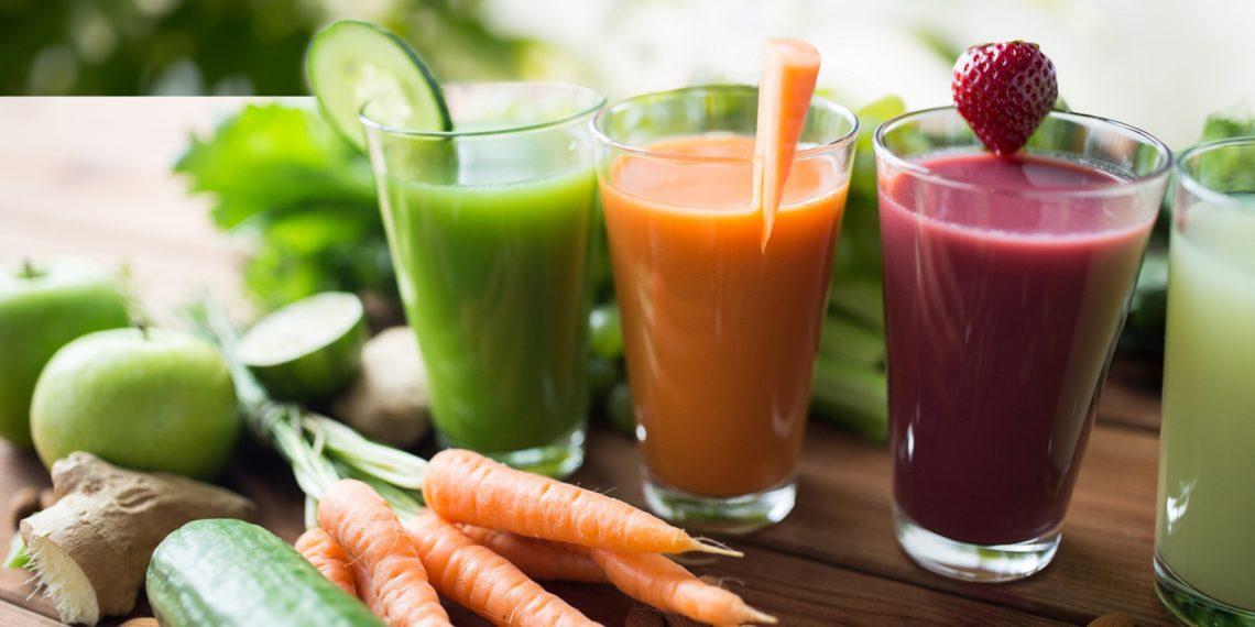 Verschiedene Smoothies und frisches Gemüse auf einem Tisch