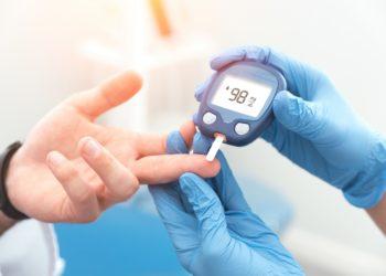 Arzt prüft bei Patienten den Blutzuckerspiegel mit einem Glukometer