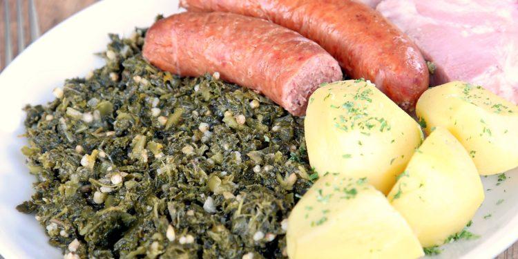 Ein Teller mit Grünkohl, Kartoffeln, Bregenwurst und Kasseler.