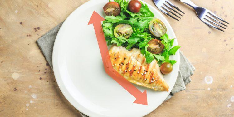 Ein Teller ist zu zwei Drittel leer und zu einem Drittel mt Hähnchenbrust und Salat belegt.