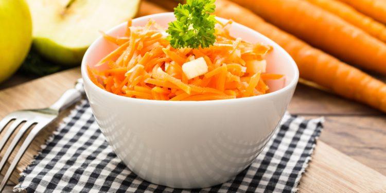 Eine Schale mit Karottensalat, Äpfeln und Möhren auf einem Holztisch.