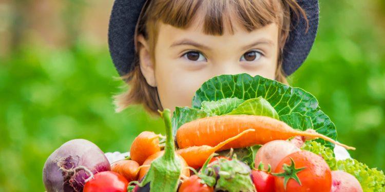 Mädchen im Freien mit verschiedenen Gemüsesorten