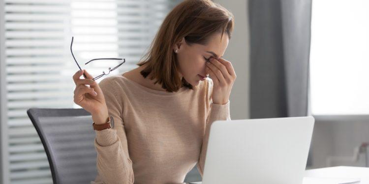 Erschöpfte junge Frau sitzt vor ihrem Laptop und fasst sich an ihre Nasenwurzel