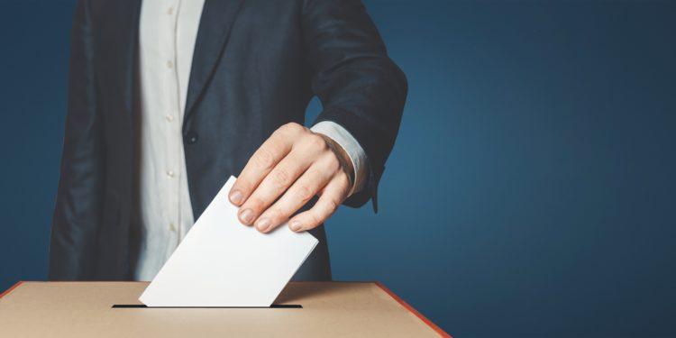 Mann steckt einen Wahlzettel in eine Wahlurne
