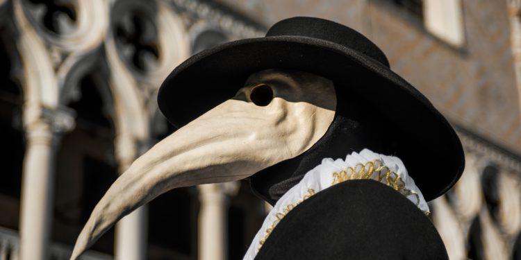 Eine als Pestdoktor mit Schnabelmaske und Hut verkleidete Person vor einem historischen Gebäude.
