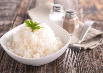 Eine kleine Schüssel gekochter Reis mit Gabel, Salz und Pfeffer auf einem Tisch